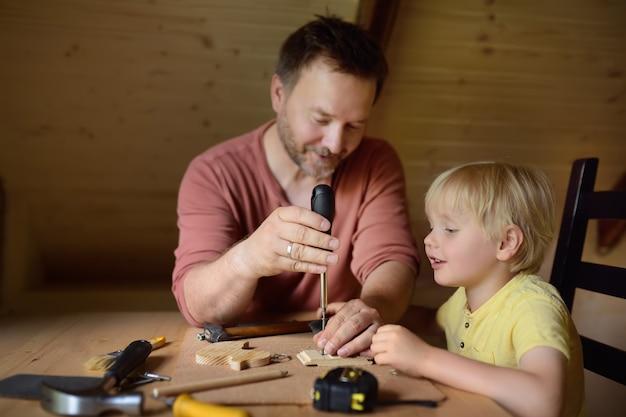 Oudere man en kleine jongen maken samen een houten speelgoed. Premium Foto