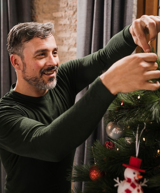Oudere man genieten van kerstboom decoratie Gratis Foto