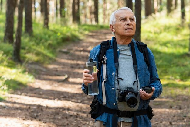 Oudere man in de natuur met camera en waterfles Gratis Foto