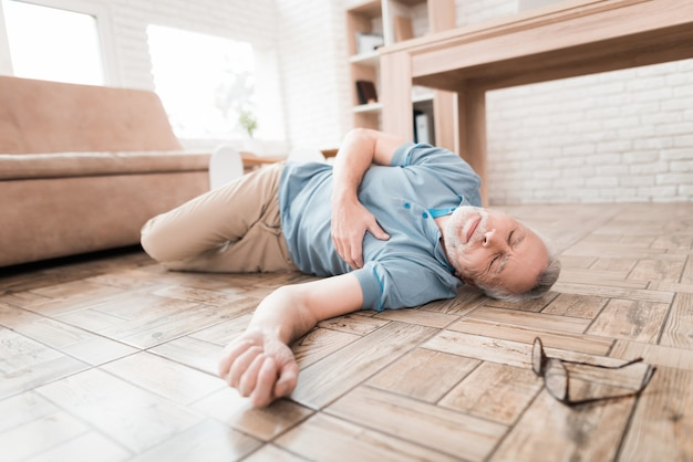 Oudere man ligt op de vloer, geklemd hart. Premium Foto