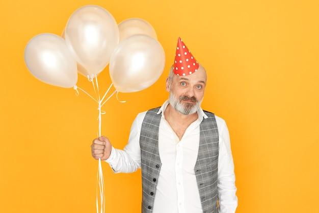 Oudere man met grijze baard vieren verjaardag. portret van knappe ongeschoren mannelijke gepensioneerde m / v met helium ballonnen plezier op verjaardagsfeestje. Gratis Foto