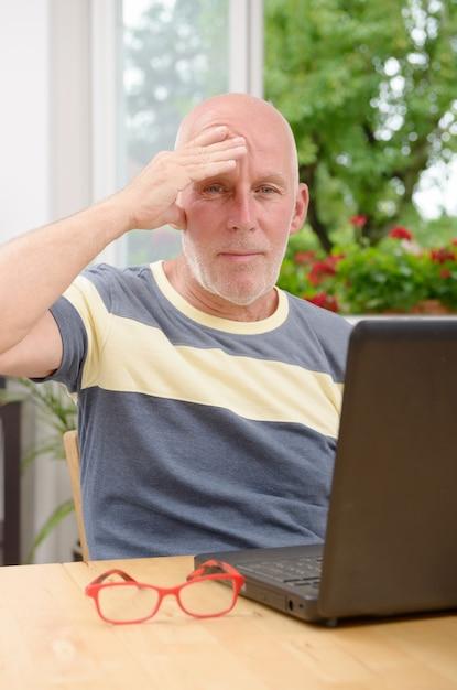 Oudere man met hoofdpijn Premium Foto