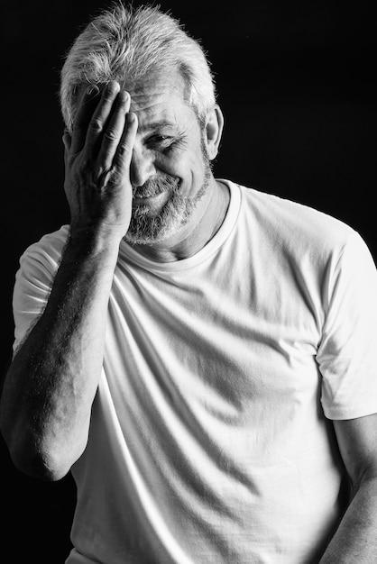 Oudere man met wit haar en baard glimlachen Gratis Foto