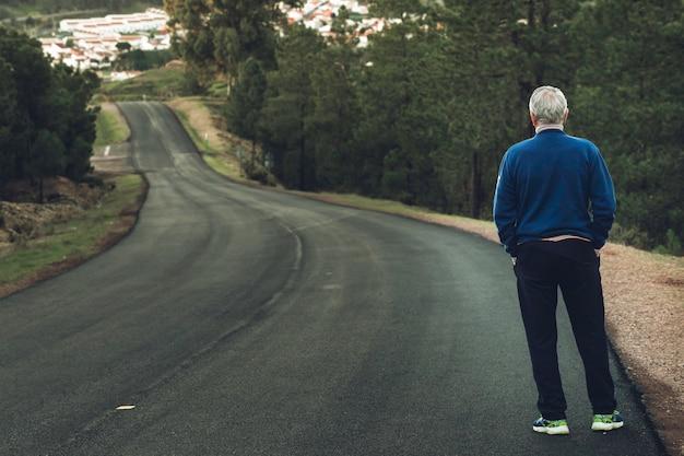 Oudere man van de rug staande op eenzame snelweg Premium Foto