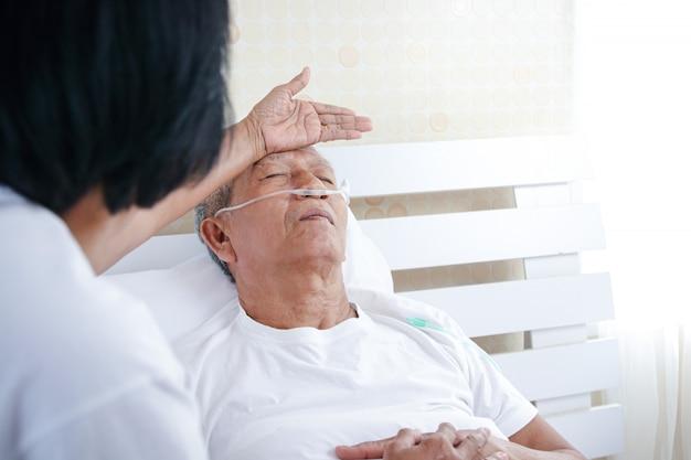 Oudere mannen met longziekte en luchtwegaandoeningen in bed in de slaapkamer er moet een vrouw voor haar zorgen. concept van gezondheidszorg voor de senior en het voorkomen van coronavirusinfectie Premium Foto