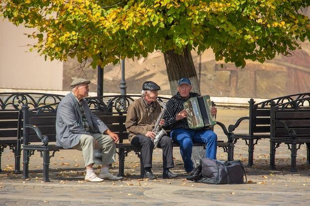 Oudere mannen zitten op een bankje in het park en spelen muziekinstrumenten in zonnige herfstdag Premium Foto