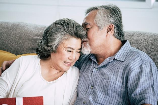 Oudere paren verrassing en geschenkdoos in de woonkamer Gratis Foto