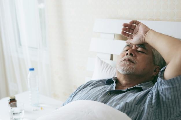 Oudere patiënten in bed, aziatische senior man patiënten hoofdpijn medische en gezondheidszorg concept Premium Foto