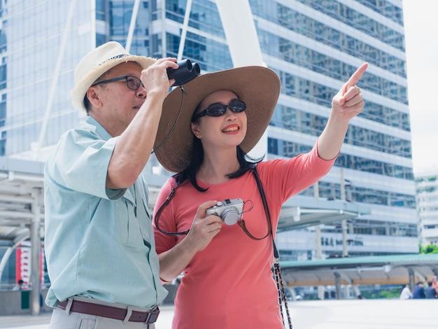 Oudere reizen in de stad, oudere man en vrouw op zoek naar iets door een verrekijker in de stad Premium Foto