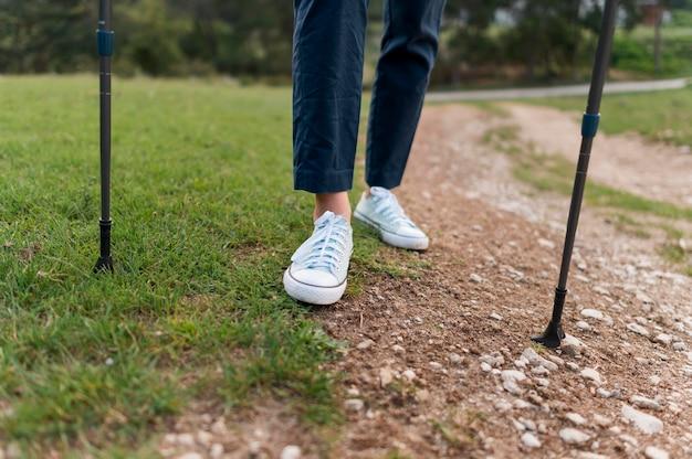 Oudere toeristenvrouw die met wandelstokken lopen Gratis Foto