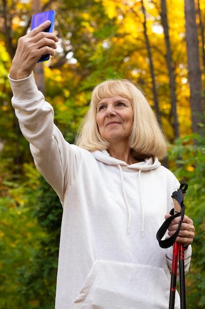 Oudere vrouw buitenshuis selfie te nemen tijdens een trektocht Gratis Foto
