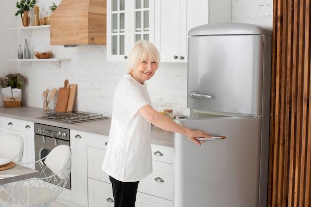 Oudere vrouw deur van koelkast openen Gratis Foto