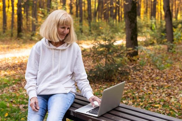 Oudere vrouw die buitenshuis laptop met behulp van Gratis Foto