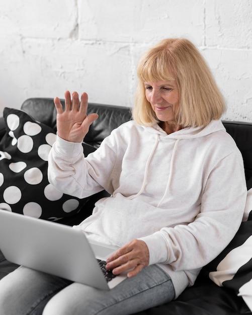 Oudere vrouw die een videogesprek met laptop heeft Gratis Foto