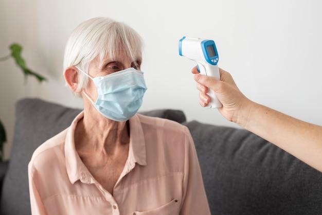 Oudere vrouw die haar temperatuur met thermometer heeft gecontroleerd Gratis Foto
