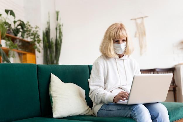 Oudere vrouw die laptop thuis met medisch masker met behulp van Gratis Foto