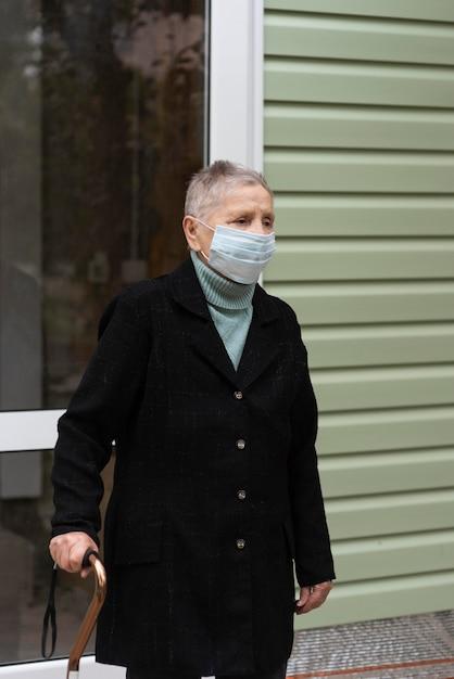 Oudere vrouw die met medisch masker een stok draagt Gratis Foto