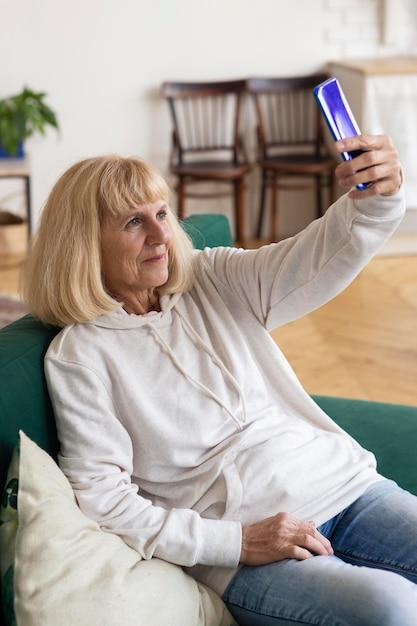 Oudere vrouw die selfie met smartphone thuis neemt Gratis Foto