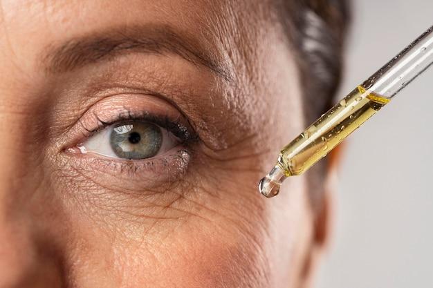 Oudere vrouw die serum gebruikt voor haar oogrimpels Premium Foto