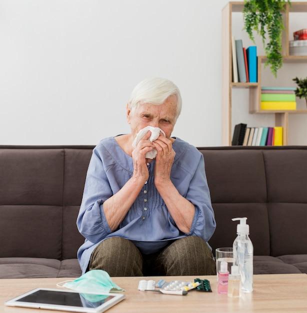 Oudere vrouw die thuis haar neus blaast Gratis Foto