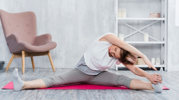 Oudere vrouw die uitrekkende yoga in woonkamer doet Gratis Foto