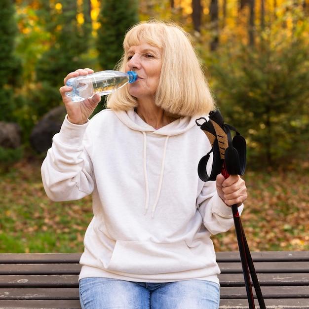 Oudere vrouw drinkwater buitenshuis tijdens trekking Gratis Foto