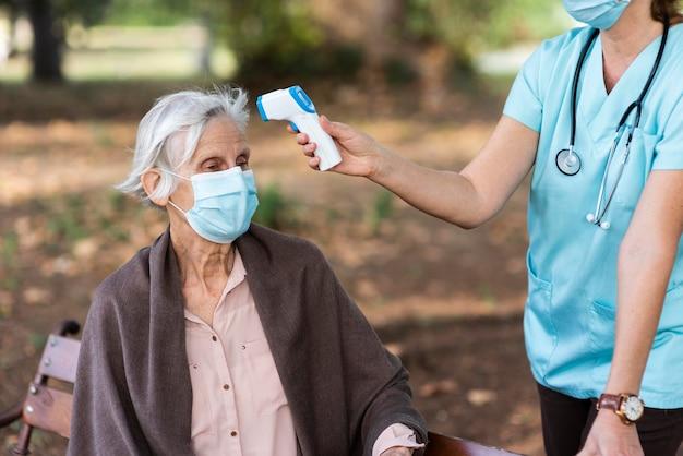 Oudere vrouw krijgt haar temperatuur gecontroleerd door verpleegster Gratis Foto