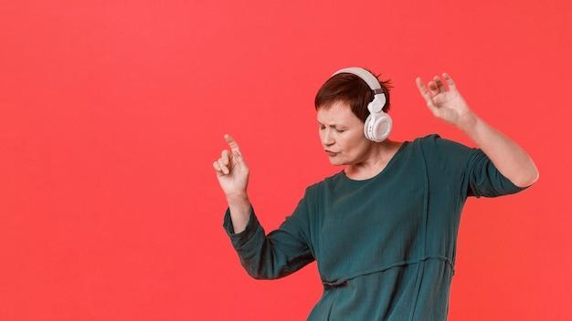 Oudere vrouw luisteren muziek en dansen Gratis Foto