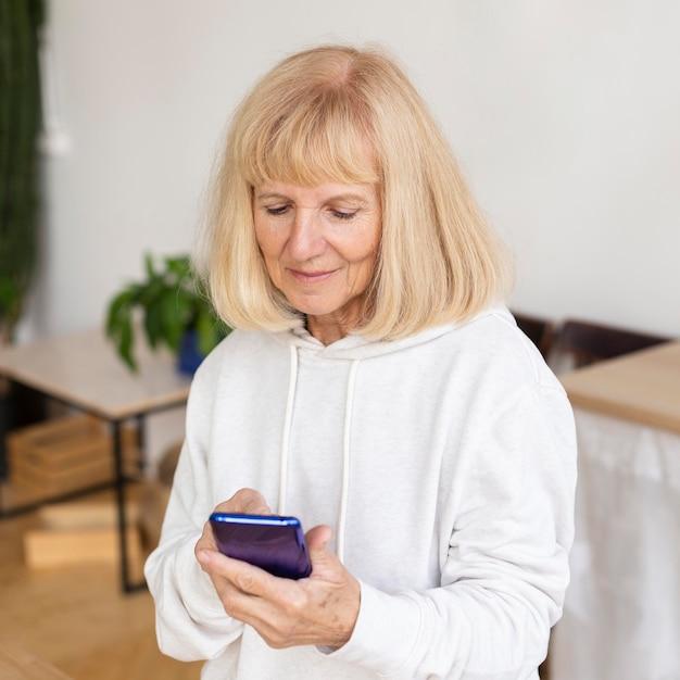Oudere vrouw met behulp van smartphone thuis Gratis Foto