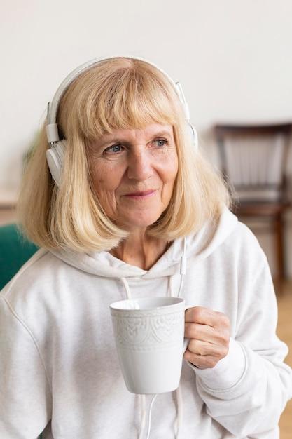 Oudere vrouw met koffie en luisteren naar muziek op de koptelefoon Gratis Foto