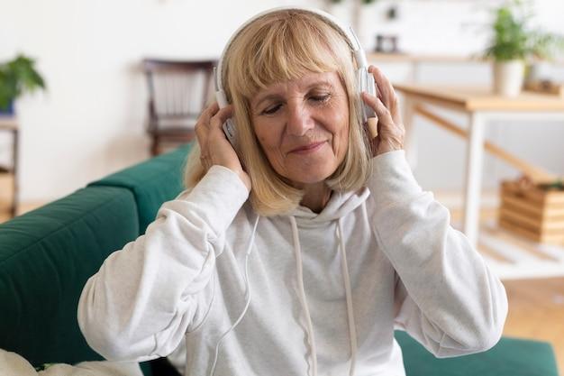 Oudere vrouw met koptelefoon thuis luisteren naar muziek Gratis Foto