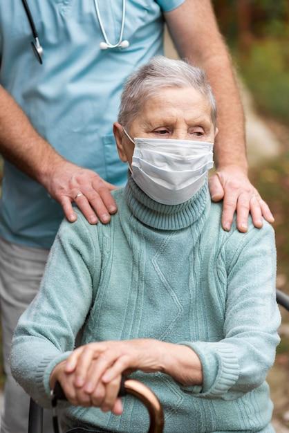 Oudere vrouw met medisch masker en verpleger bij verpleeghuis Gratis Foto