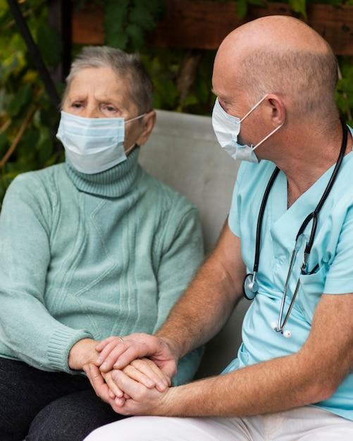 Oudere vrouw met medisch masker en verpleger Gratis Foto