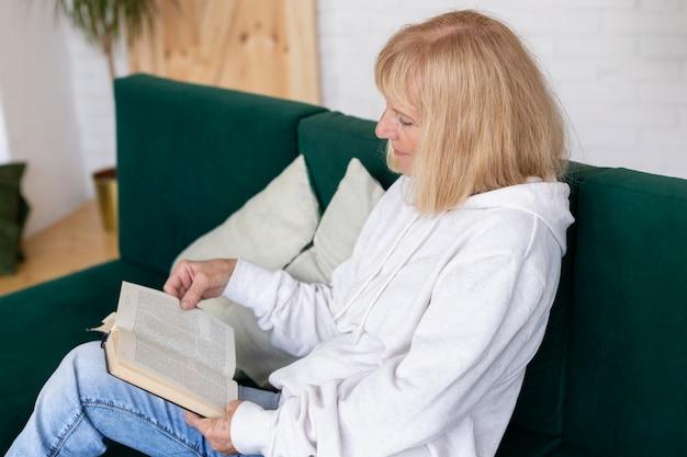 Oudere vrouw op de bank die thuis een boek leest Gratis Foto