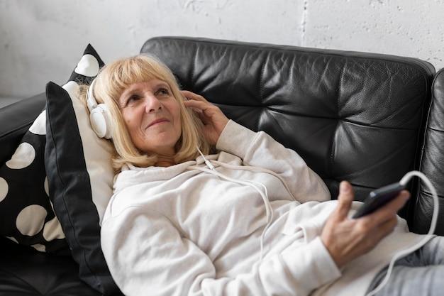Oudere vrouw op de bank luisteren naar muziek op de koptelefoon Gratis Foto