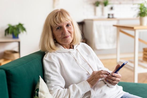 Oudere vrouw thuis op de bank met behulp van smartphoneapparaat Gratis Foto