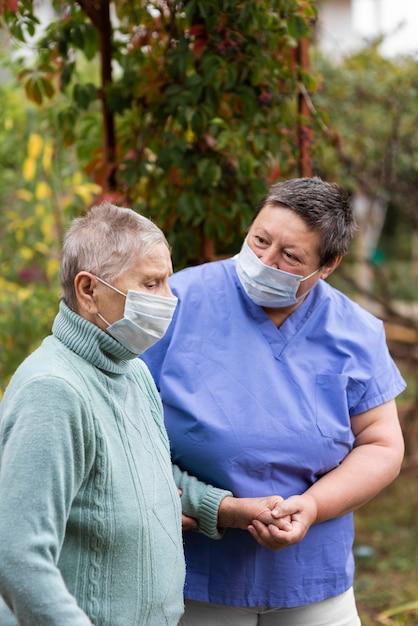 Oudere vrouw wordt verzorgd door vrouwelijke verpleegster Gratis Foto