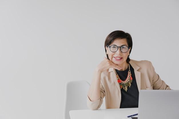 Oudere vrouw zittend op haar kantoor met copyspace Gratis Foto