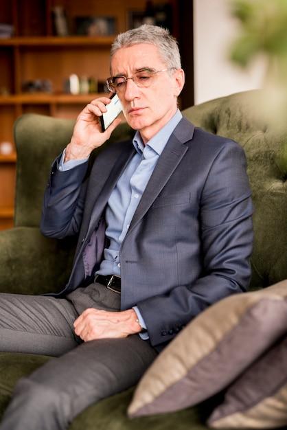 Oudere zakenman die telefonisch spreekt Gratis Foto