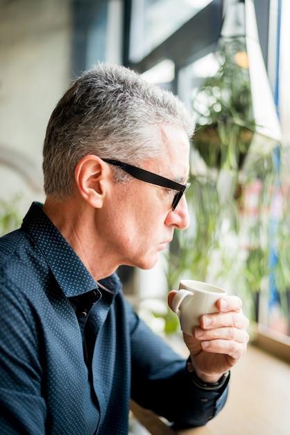 Oudere zakenman die van koffie heeft Gratis Foto