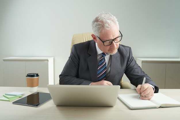 Oudere zakenman gericht op werk Gratis Foto