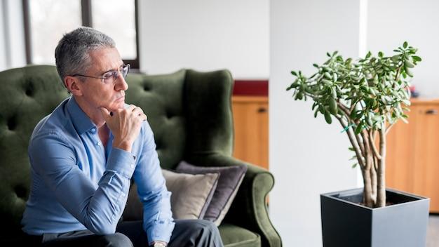 Oudere zakenman poseren op een sofa Gratis Foto