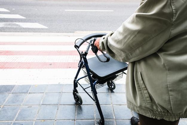 Ouderling die wacht om een zebrapad over te steken, ondersteund door een rollator. Premium Foto