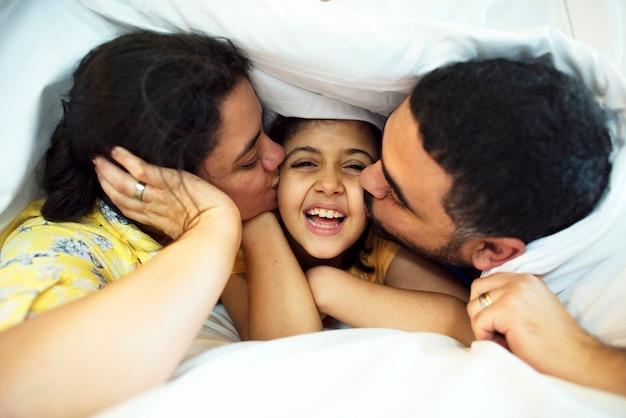 Ouders die dochter kussen op de wangen geven Premium Foto