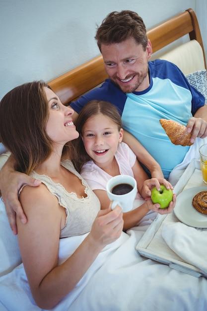 Ouders die op bed met dochter zitten en ontbijt hebben Premium Foto