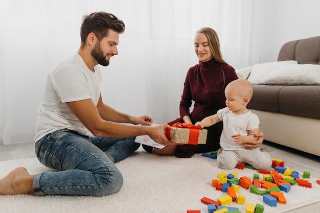 Ouders die thuis een geschenk aan hun baby geven Gratis Foto