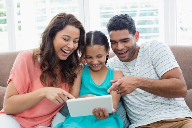 Ouders en dochter die digitale tablet in woonkamer gebruiken Premium Foto