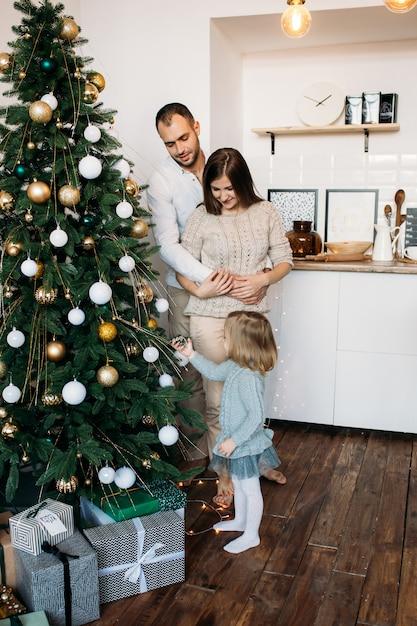 Ouders en dochtertje versieren kerstboom thuis. vrolijk kerstfeest en een gelukkig nieuwjaar! Premium Foto