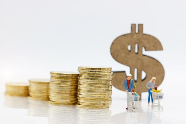Ouders en kind met het winkelen kaart die zich vóór muntstukkenstapel en dollarteken bevinden. Premium Foto