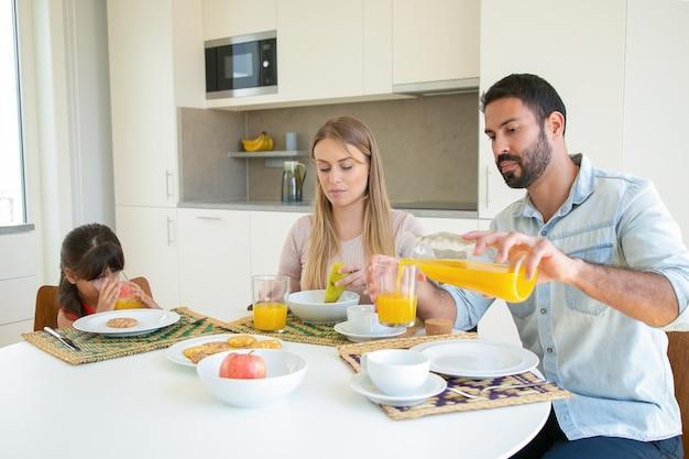 Ouders en kind zitten aan de eettafel met schotel, fruit en koekjes, gieten en vers sinaasappelsap drinken. Gratis Foto